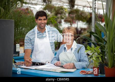 Jeune homme avec de hauts femme travaillant dans un centre de jardinage