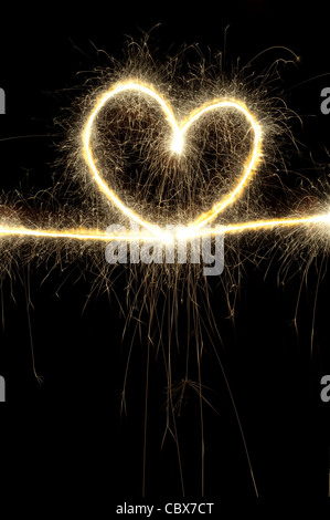 Forme de coeur fait avec sparkler la nuit.