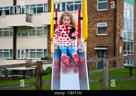 Enfant de 3 ans enfant fille Toddler playing glissant sur une diapositive dans une aire de jeux pour enfants Banque D'Images