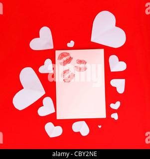 Carte vierge avec des baisers rouge isolé sur fond rouge, conceptual image d'amour et de la Saint-Valentin Banque D'Images