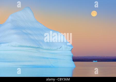 Iceberg au coucher du Soleil et lune au Hall Bredning, Scoresbysund, Groenland Banque D'Images