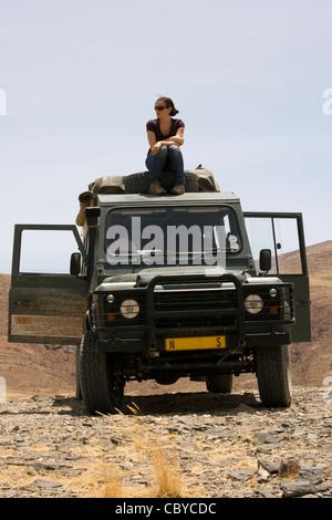 Jeune femme assise sur le dessus de véhicule safari - Purros Conservancy - Kaokoland, région de Kunene, Namibie, Banque D'Images