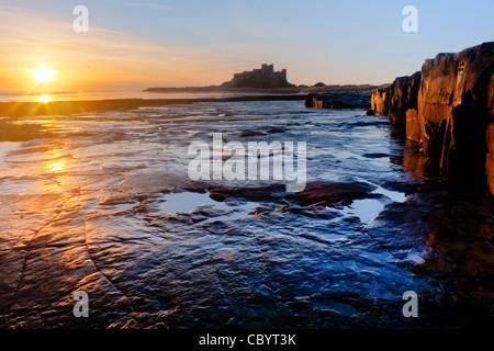 Lever du soleil près de Château de Bamburgh sur la côte nord-est de l'Angleterre Banque D'Images