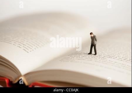 Une petite figure d'un homme marchant sur un livre ouvert - image conceptuelle pour l'alphabétisation et de la lecture Banque D'Images