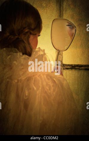 Vue arrière d'une femme à la recherche dans un miroir Banque D'Images