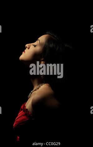 Belle femme en robe rouge debout dans l'obscurité Banque D'Images