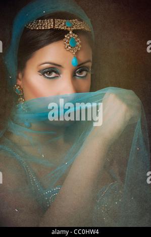 Belle femme indienne se cachant le visage avec un voile bleu Banque D'Images