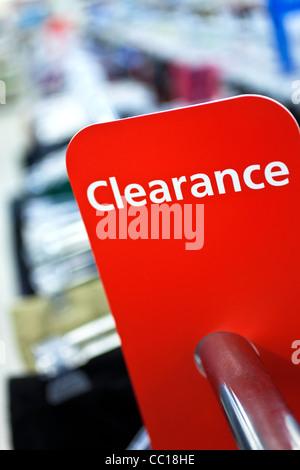 Une autorisation de vente rouge signe sur rail de vêtements dans une boutique Banque D'Images