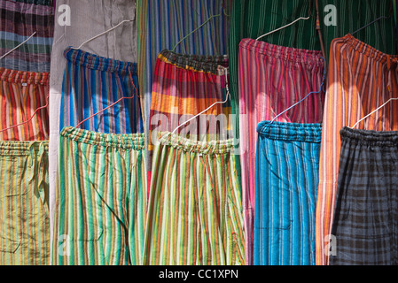 Une variété de pantalons en tissu très coloré de l'accrocher à un affichage dans le marché d'Otavalo, Équateur. Banque D'Images
