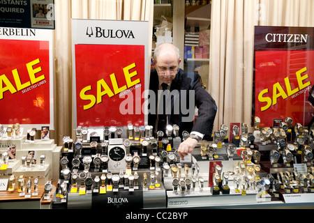 Un bijoutier ajustant sa vitrine dans une vente, Cambridge UK Banque D'Images