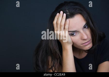 Jeune femme déprimée sur fond noir Banque D'Images