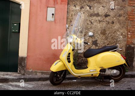 Un scooter jaune garé à l'extérieur d'une petite porte d'italien en Sicile, Italie. Banque D'Images