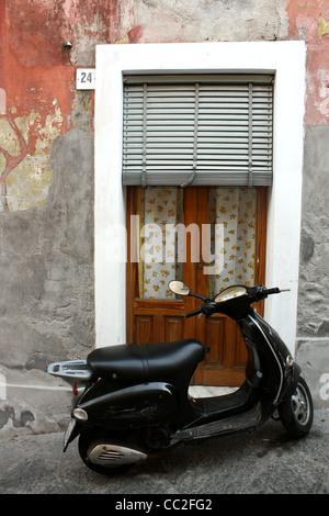 Un scooter noir stationné à l'extérieur d'une petite porte d'italien en Sicile, Italie. Banque D'Images