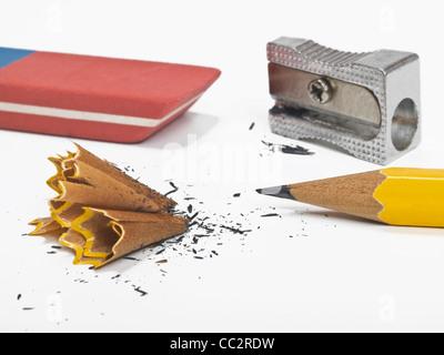 Un crayon aiguisé, à côté sont une gomme, un taille-crayons et les copeaux