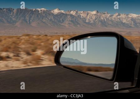 La réflexion en miroir de voiture la conduite à travers le désert près de Lone Pine en Californie. Banque D'Images