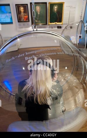 Jeune femme à l'écoute des enregistrements de Bach assis dans un fauteuil bulle. Maison de Bach, Bachhaus Eisenach, Banque D'Images