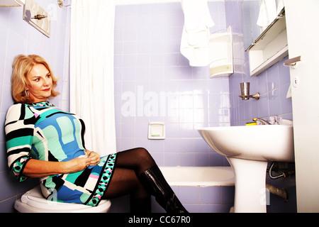 Vintage / femme / shoot rétro fatale. Femme assise sur la toilette. Banque D'Images