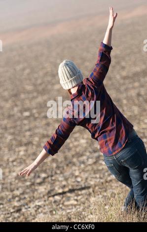 Happy young woman walking dans un champ à la campagne