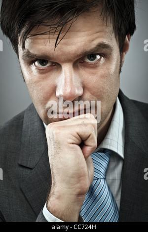Jeune homme avec une expression de concentration intense Banque D'Images