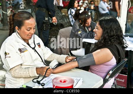 Jolie jeune femme mexicaine sourit comme infirmière prend sa pression artérielle dans la clinique de plein air parrainé Banque D'Images