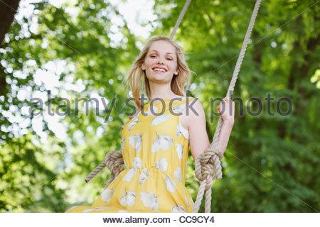 Portrait of smiling woman on swing sous les arbres Banque D'Images