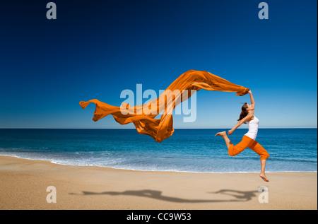 Belle jeune femme sautant sur la plage avec un tissu de couleur Banque D'Images