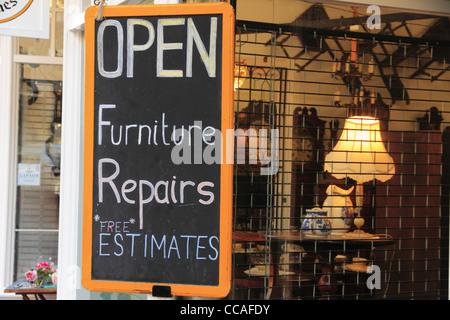 Inscrivez-vous publicité réparation de meubles réparation et devis gratuits dans un magasin d'antiquités de fenêtre. Banque D'Images