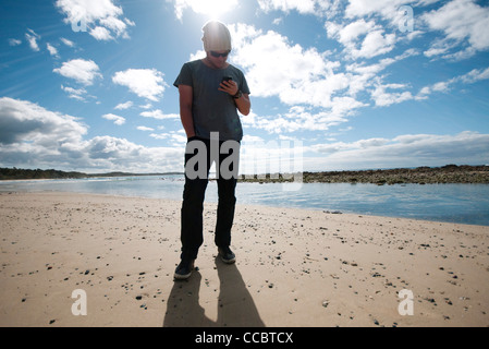 Man Standing on beach, looking at cell phone Banque D'Images