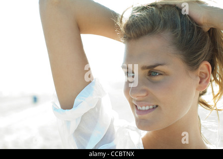 Smiling woman with hands in hair Banque D'Images