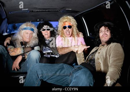 Cheerful male friends sitting in a limousine Banque D'Images