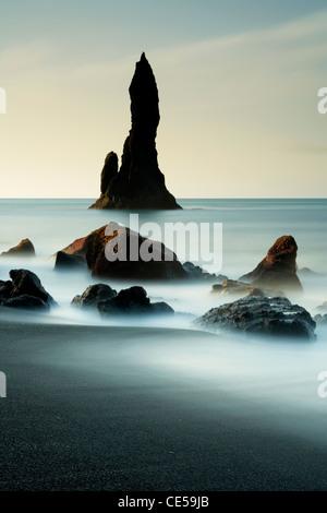 En ondes lave volcanique noire autour de piles de la mer sur la côte d'Islande Vik Banque D'Images