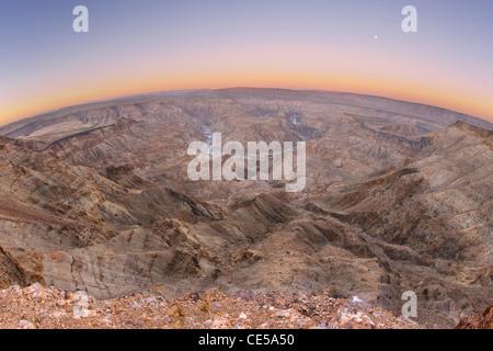 Objectif fish-eye view de la pleine lune se couche sur le Fish River Canyon dans le sud de la Namibie à l'aube. Banque D'Images