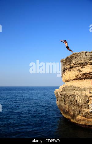 Un homme est d'une haute falaise de trempage Banque D'Images