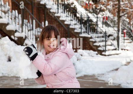 L'hiver portrait of a smiling little girl playing in the snow jetant une grande boule de neige. Banque D'Images