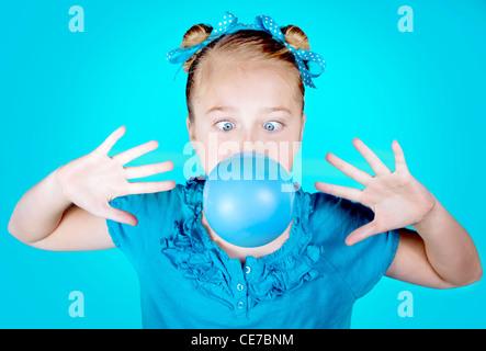 Un cross eyed girl wearing blue avec les yeux bleus et le blue bow, soufflant une bulle bleue. Sur un fond bleu Banque D'Images