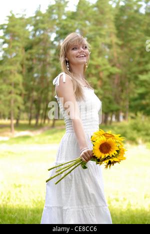 Belle jeune femme heureuse avec des tournesols dans la robe blanche Banque D'Images