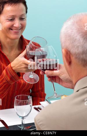 Photo d'un couple dans un restaurant toasting leurs verres de vin rouge, Banque D'Images