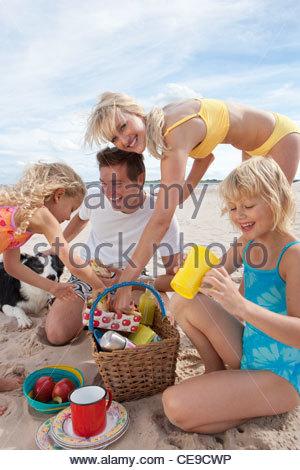 Famille avec chien pique-nique sur sunny beach Banque D'Images