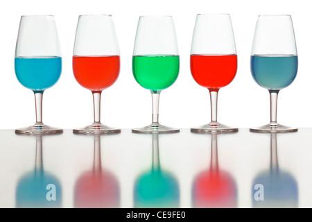 Verres de liquide de couleur photographié sur un fond blanc