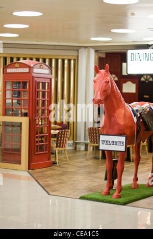 Cheval Rouge modèle et téléphone rouge fort dans l'aéroport d'Heathrow Londres Angleterre Banque D'Images
