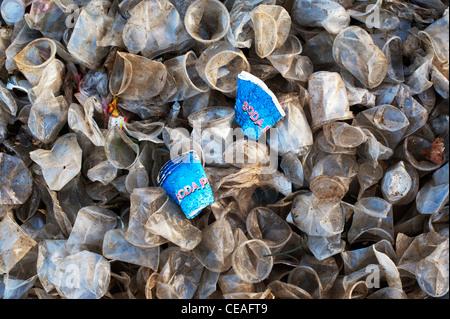 Jetée de soda en plastique papier entre les tasses de thé dans la campagne indienne. L'Andhra Pradesh, Inde