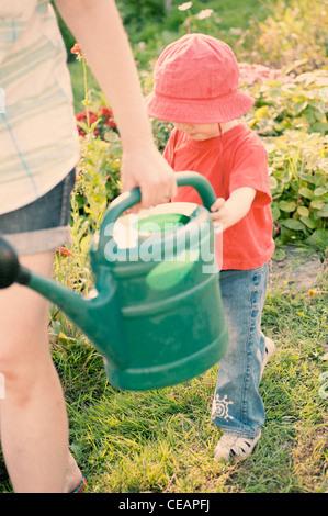 Jeune fille aider sa mère dans le jardin Banque D'Images