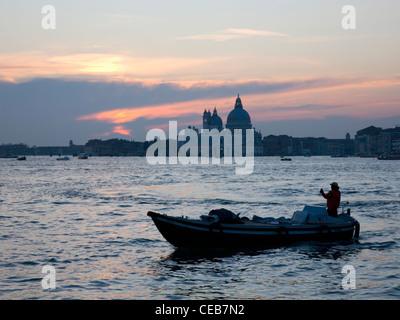 Venise, Vénétie, Italie. Au coucher du soleil sur la lagune, à la basilique Santa Maria della Salute, petit bateau en premier plan.