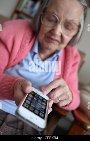 Femme âgée l'adoption de nouvelles technologies, écran tactile iPhone, smartphone, à la maison des photographes (studio) Leiston, Suffolk, UK.
