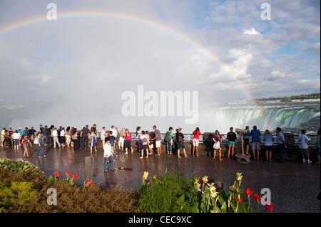 Les touristes regardant arc dans la pulvérisation à Niagara Falls, Canada. Banque D'Images