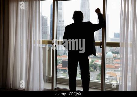 Vue arrière de l'homme d'affaires à la recherche de bâtiments à fenêtre Banque D'Images