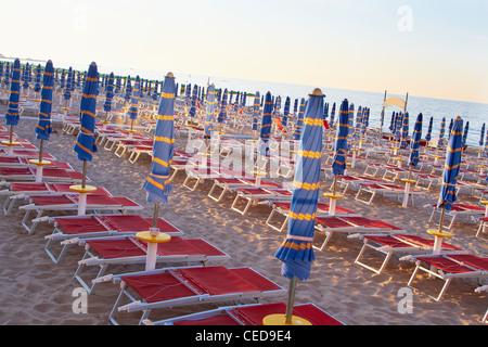Parasols et chaises de plage dans une rangée sur la plage Banque D'Images