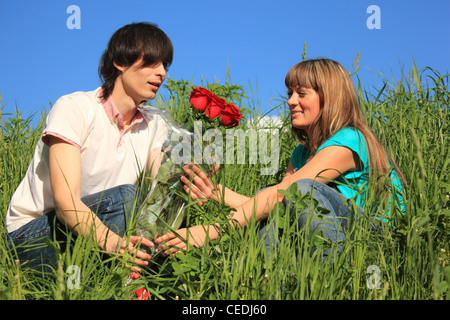 Guy donne à girl bouquet de roses parmi l'herbe Banque D'Images