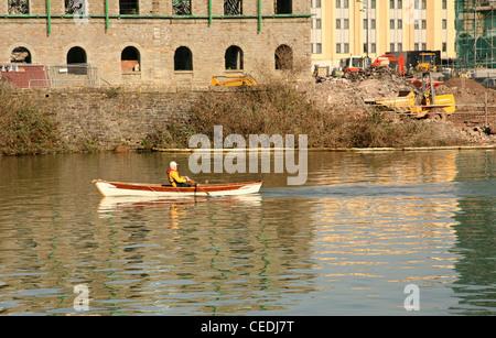 Février 2008 - l'homme d'un petit bateau à rames sur une grande rivière Banque D'Images