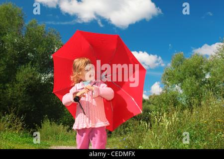 Petite fille avec parapluie rouge piscine en été Banque D'Images